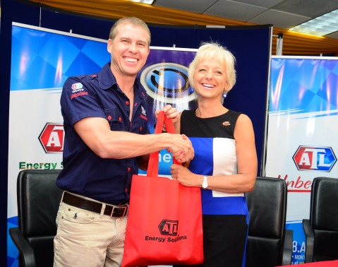 Deputy Chairman of the ATL Group Adam Stewart (left) presents an ATL Energy Solutions goodie tote bag to JPS head Kelly Tomblin following the announcement of a partnership between ATL and JPS. The partnership will see ATL extending its distribution of alternative and energy-efficient products through JPS' Customer Service eStore outlets.